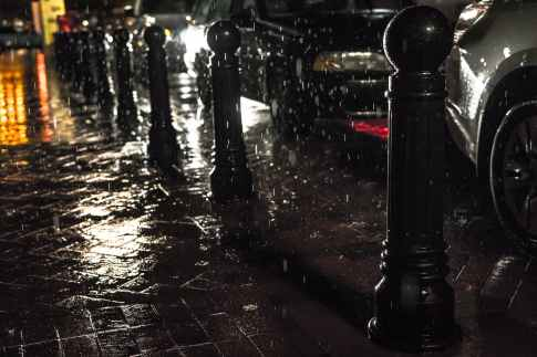 black posts on black pavement beneath falling rain